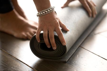 Fitnessmatte, Ausrüstung für den Sportunterricht. Wohlfühlkonzept. Mädchen, das Fitnessmatte vor oder nach dem Training im Yoga-Studio-Club, zu Hause oder im Fitnessstudio auf Holzboden ausrollt. Hände und Beine schließen sich