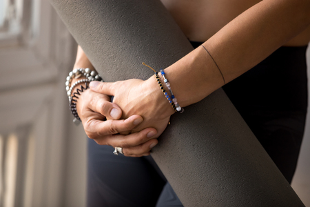 Female hands holding yoga or fitness mat before practicing yoga and working out, wearing wrist bracelets, indoor hands close up. Healthy lifestyle, hobby, beauty, well being concept