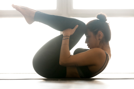 Young sporty yogi woman practicing yoga, doing Knees to Chest exercise, Apanasana pose, working out, wearing sportswear, grey pants, bra, indoor full length, at yoga studio