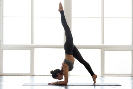 Young sporty attractive woman practicing yoga, doing Pincha Mayurasana exercise, handstand pose, working out, wearing sportswear, grey pants, top, indoor full length, at yoga studio Stockfoto