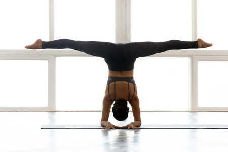 Young yogi attractive woman practicing yoga, doing Pincha Mayurasana exercise, handstand pose, working out, wearing sportswear, grey pants, top, indoor full length, at yoga studio, rear view Stockfoto