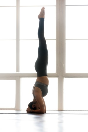 Young yogi attractive woman practicing yoga, doing headstand exercise, salamba sirsasana pose, working out, wearing sportswear, grey pants, top, indoor full length, at yoga studio, side view, vertical