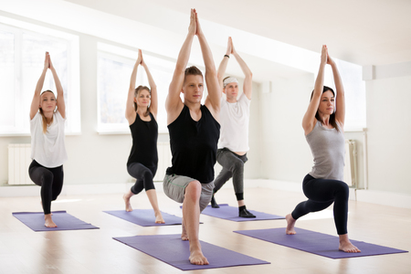 Group of young sporty people practicing yoga lesson, doing Warrior one exercise, Virabhadrasana I pose, working out, indoor, students training in club, studio. Well-being concept