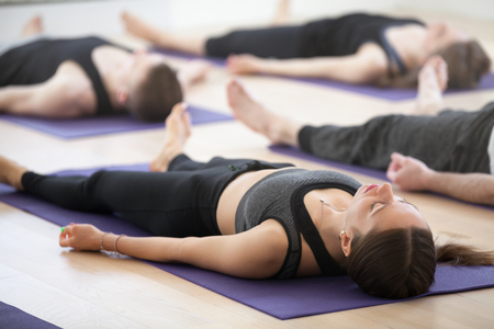 Group of young sporty people practicing yoga lesson, doing Dead Body, Savasana, exercise Corpse pose, working out, indoor, students training in club, studio close up. Well-being concept Stock Photo