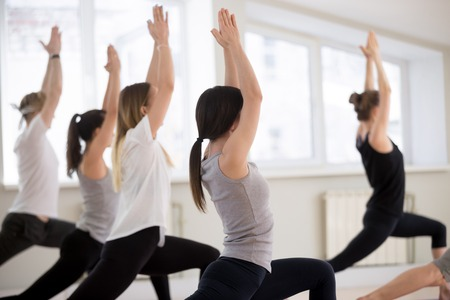 Group of young sporty people practicing yoga lesson, doing Warrior one exercise, Virabhadrasana I pose, working out, indoor, students training in club, studio close up, back view. Well-being concept