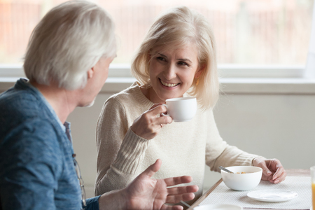 Smiling beautiful middle aged mature woman drinking coffee tea listening to older man talking during breakfast, senior happy family couple eating having pleasant conversation on date at home in caf Foto de archivo