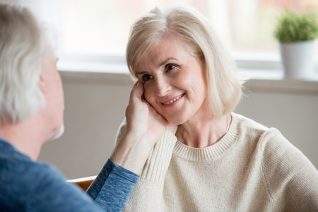 Caring senior husband touching beautiful face of smiling middle aged happy wife looking at husband with love devotion, old family couple enjoying tenderness, giving support understanding concept