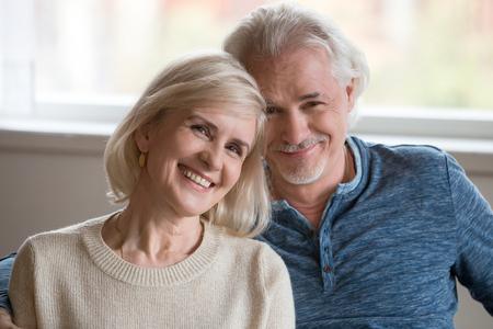 Headshot-Porträt eines glücklichen romantischen Paares mittleren Alters, das sich im Haus ausgibt, lächelnde alte Familie im Ruhestand, die das Betrachten der Kamera umarmt und älteren reifen Mann und Frau liebt, die Bindung zusammen umarmen