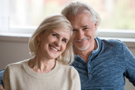 Headshot portrait of happy middle aged romantic couple dating posing indoors, smiling retired old family embracing looking at camera, loving senior mature man and woman hugging bonding together Archivio Fotografico