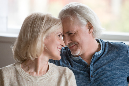 Happy middle aged romantic couple touching noses having fun enjoying sincere love feelings together, smiling senior older family bonding looking at each other, mature man and woman dating concept