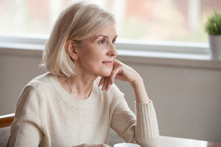 Thoughtful middle aged mature woman looking away drinking coffee tea thinking of future, dreamy beautiful senior lady relaxing alone dreaming hoping contemplating sitting at table lost in thoughts