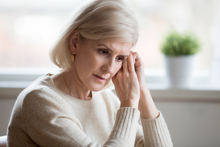 Thoughtful sad mature middle aged woman feeling blue melancholic worried concerned about problems, upset serious depressed senior old lady widow thinking of anxiety depression, grieving lost love Reklamní fotografie