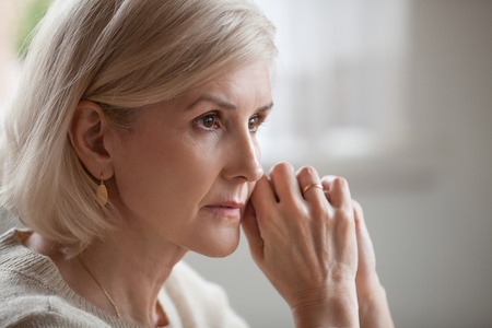 Thoughtful serious anxious mature senior woman feeling blue worried about problems, pensive upset sad middle aged grey haired lady looking away thinking of loneliness, getting older and depression