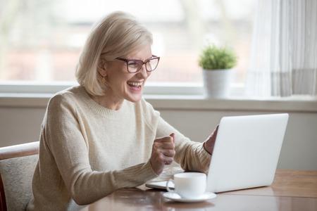Glücklicher reifer älterer Geschäftsfrauengewinner mittleren Alters aufgeregt durch das Lesen der guten Nachrichten beim Betrachten des Laptops, der glücklichen älteren älteren Dame, die das Feiern des Online-Gebotswettgewinns oder des großartigen Ergebnissiegkonzepts beobachtet