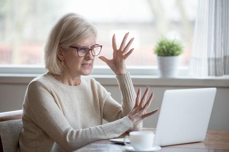 怒っているストレスの上級中年のビジネスウーマンは、コンピュータの問題に悩まされ、古いサラリーマンはラップトップを立ち往生嫌い、狂った成熟した女性は悪いオンラインニュース、データ損失、ソフトウェアの失敗に不満を抱いています