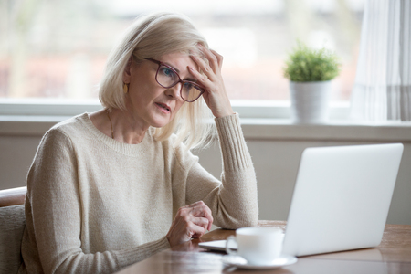 Thoughtful confused mature business woman concerned thinking about online problem looking at laptop, frustrated worried senior middle aged female reading bad email news, suffering from memory loss