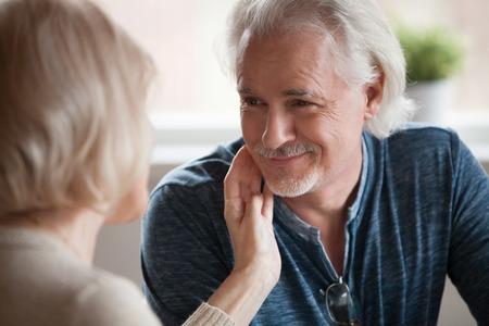 Femme d'âge moyen bienveillante caressant doucement le visage de l'homme mûr souriant beau mari regardant sa femme bien-aimée, famille âgée appréciant l'amour, la compréhension, les sentiments chaleureux, les plus vieux couple romantique datant Banque d'images
