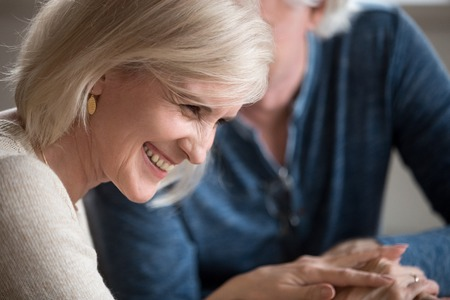Happy middle aged senior woman with beautiful face laughing flirting with beloved older man, smiling loving wife enjoying humor talk with elderly husband, mature family couple having fun on date Stock Photo