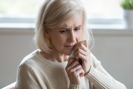 Upset middle aged woman wiping tears crying feeling depressed hopeless lonely after divorce, desperate old senior widow thinking of disease, sorrow or grief, mature elderly lady mourning concept Stock Photo