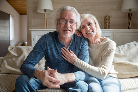 Smiling senior middle aged vloggers couple looking talking at camera recording video blog at home, happy friendly mature old family making videocall sitting on sofa, elderly lifestyle vlog concept Stock Photo