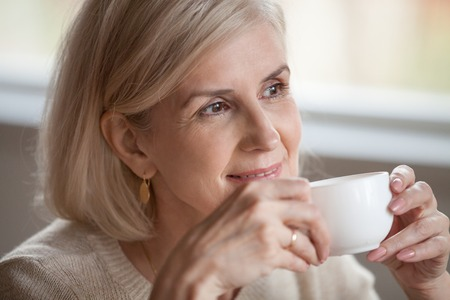 Thoughtful happy middle aged senior woman with beautiful face looking away drinking morning coffee, smiling mature old lady holding tea cup relaxing with positive thoughts dreaming enjoying wellbeing
