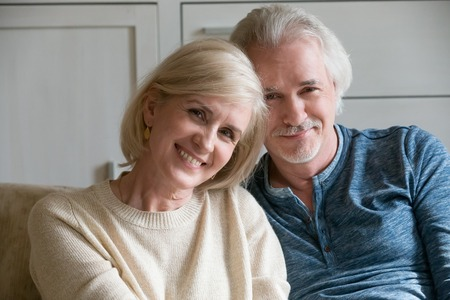 Headshot portrait of smiling loving mature old man and woman dating feeling happy together, middle aged senior retired romantic couple family embracing looking at camera bonding posing at home Stock Photo