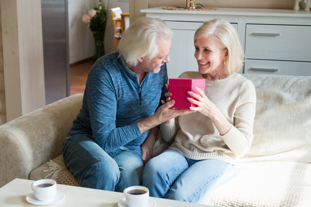 Loving older husband presenting romantic birthday gift to mature smiling wife, caring elderly man giving pink box with present to middle aged happy woman, senior couple celebrating together at home
