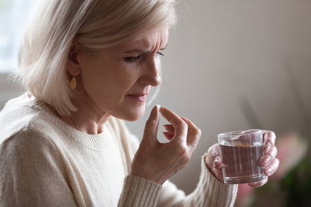 Upset senior ill woman holding pill and glass or water taking painkiller medicine to relieve headache pain, sad middle aged elderly lady worried about side effects of meds for old person concept
