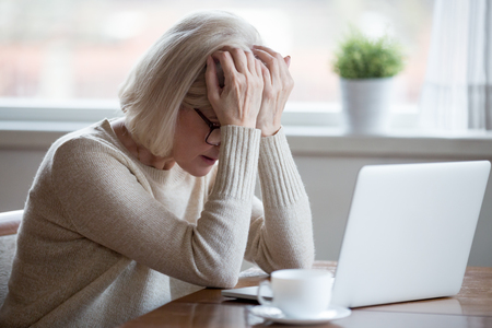 Upset depressed mature middle aged woman in panic holding head in hands in front of laptop frustrated by bad news, online problem or being fired by email feeling desperate shocked exhausted concept Stockfoto