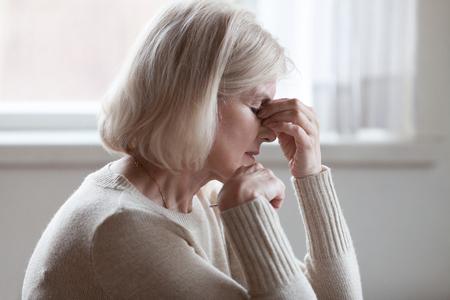 Vermoeide overstuur oudere vrouw van middelbare leeftijd masseert neusbrug gevoel van vermoeidheid van de ogen of hoofdpijn probeert pijn te verlichten, verdrietig senior volwassen dame uitgeput depressief vermoeid duizelig moe denken aan problemen Stockfoto