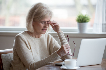 Sconvolto affaticato oberato di lavoro senior donna matura di affari che toglie gli occhiali stanco del lavoro al computer, esaurito dipendente di mezza età soffre di visione sfocata dopo un lungo uso del laptop, problema di affaticamento degli occhi