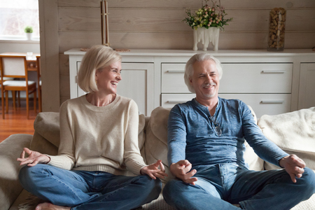 Mature couple having fun laughing doing yoga together at home, happy middle aged family sitting in lotus pose looking at each other smiling learning to meditate, healthy senior people lifestyle