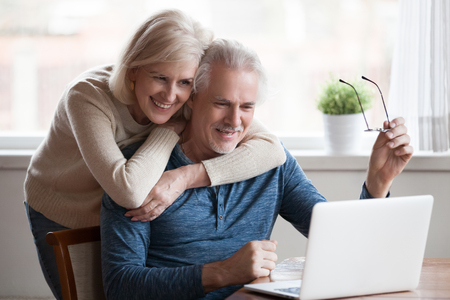 Senior middle aged happy couple embracing using laptop together, smiling elderly family reading news, shopping online at home, older people and computer or good vision after laser correction concept