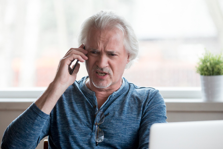 Angry furious senior mature man caller arguing talking on the phone disputing complaining about problems with laptop, mad emotional male shouting speaking by mobile calling customer support