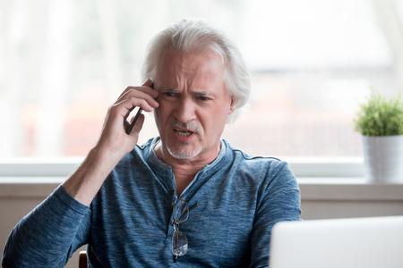 Chiamante arrabbiato furioso senior uomo maturo sostenendo parlando al telefono disputando lamentandosi di problemi con il computer portatile, arrabbiato maschio emotivo gridando parlando da cellulare chiamando l'assistenza clienti