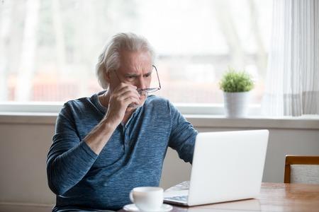 Schockierter frustrierter älterer reifer Mann, der die Brille abnimmt, um auf Laptop zu schauen, der schockierende Online-Nachrichten zu Hause liest, betonte besorgten besorgten alten Mann mittleren Alters, der durch schlechte E-Mail-Nachrichten oder Computerprobleme verwirrt ist