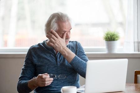 Erschöpfter reifer alter Mann, der nach langer Computernutzung die Brille abnimmt, die unter müden, trockenen, gereizten Augen leidet. Älterer Mann mittleren Alters verspürt ein Problem mit der Augenbelastung oder eine verschwommene Sicht, wenn er zu Hause am Laptop arbeitet