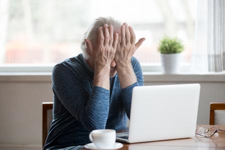 El hombre maduro mayor fatigado se siente cansado de la computadora frotándose los ojos secos e irritados para aliviar el dolor o llorando molesto frustrado, anciano de mediana edad que sufre de fatiga visual después del concepto de uso prolongado de la computadora portátil