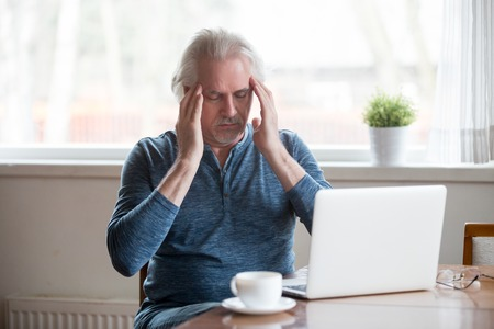 Tired fatigued middle aged senior man touching temples feeling headache migraine working on laptop at home, old elderly mature man trying to remember or focus suffering from memory loss disorder Stockfoto