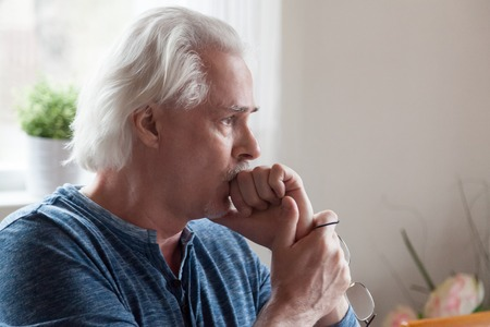 Worried serious mature senior man feeling melancholic anxious about problems making difficult decision, upset thoughtful sad middle aged old male looking away thinking of loneliness and depression