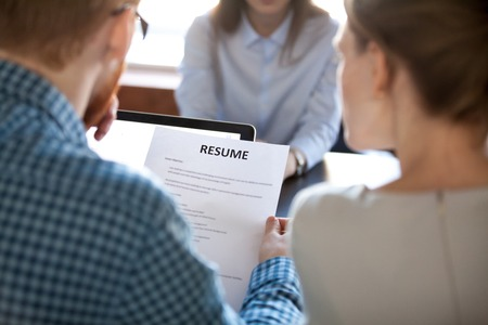 Reading resume at job interview concept, hr employer holding cv examining skills and experience of vacancy position candidate making first impression, employment and hiring, staff recruiting concept Stock Photo