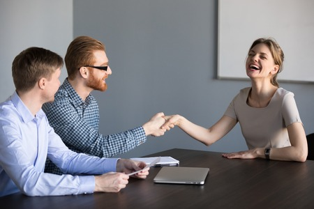 Happy job applicant shaking hand getting hired laughing at funny joke, positive work candidate handshaking friendly hr making good impression enjoying successful interview, humor and hiring concept