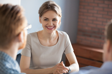 Confident millennial businesswoman smiling looking at male partner at business meeting, happy job applicant being interviewed by hr managers, good performance, recruiting and first impression concept 스톡 콘텐츠 - 109334043