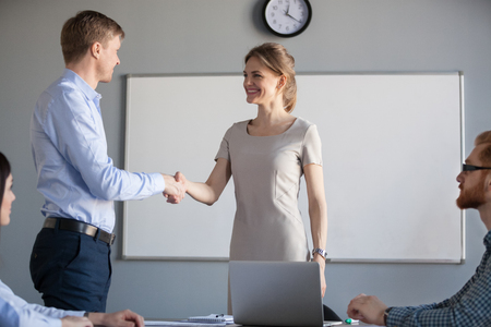 Smiling friendly businesswoman shaking hand welcoming male business partner at negotiations, female ceo greeting new team member with handshake at group meeting, respect or first impression concept