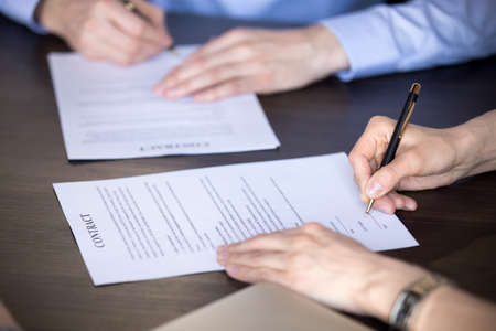 Close up view of male and female hands signing two contracts, man and woman put written signature on legal papers becoming new partners filling business document form promising good partnership deal