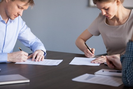 Partners or deal parties signing business documents, businessman and businesswoman put signatures on paper contracts at meeting agreeing on terms promising partnership after successful negotiation Stock Photo