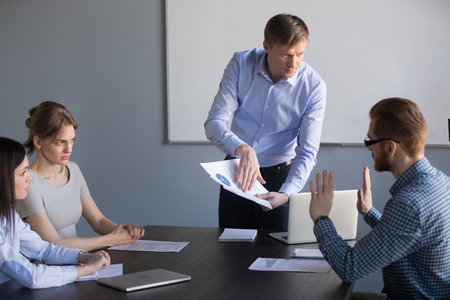 Stressed employee disagreeing with boss blaming for mistake in financial report, dissatisfied ceo team leader arguing with worker about bad work charging fault upon duties failure or demanding result Stockfoto