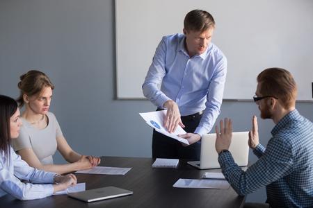 Gestresster Mitarbeiter, der nicht damit einverstanden ist, dass der Chef für Fehler im Finanzbericht verantwortlich gemacht wird, unzufriedener CEO-Teamleiter, der sich mit dem Arbeitnehmer über schlechte Arbeit bei der Erhebung von Fehlern bei Dienstausfall oder anspruchsvollem Ergebnis auseinandersetzt Standard-Bild