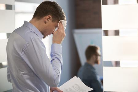 Nervöser verschwitzter Geschäftsmannsprecher, der Rede vorbereitet, die Angst davor hat, öffentlich zu sprechen, feuchte Stirn mit Taschentuch abwischen, das sich gestresst oder besorgt über das Schwitzen vor wichtiger Büroleistung fühlt.