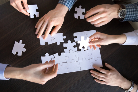 Top close up view of male and female hands engaged in assembling jigsaw puzzle as concept of successful cooperation teamwork, finding business solution together, teambuilding, help, unity and support